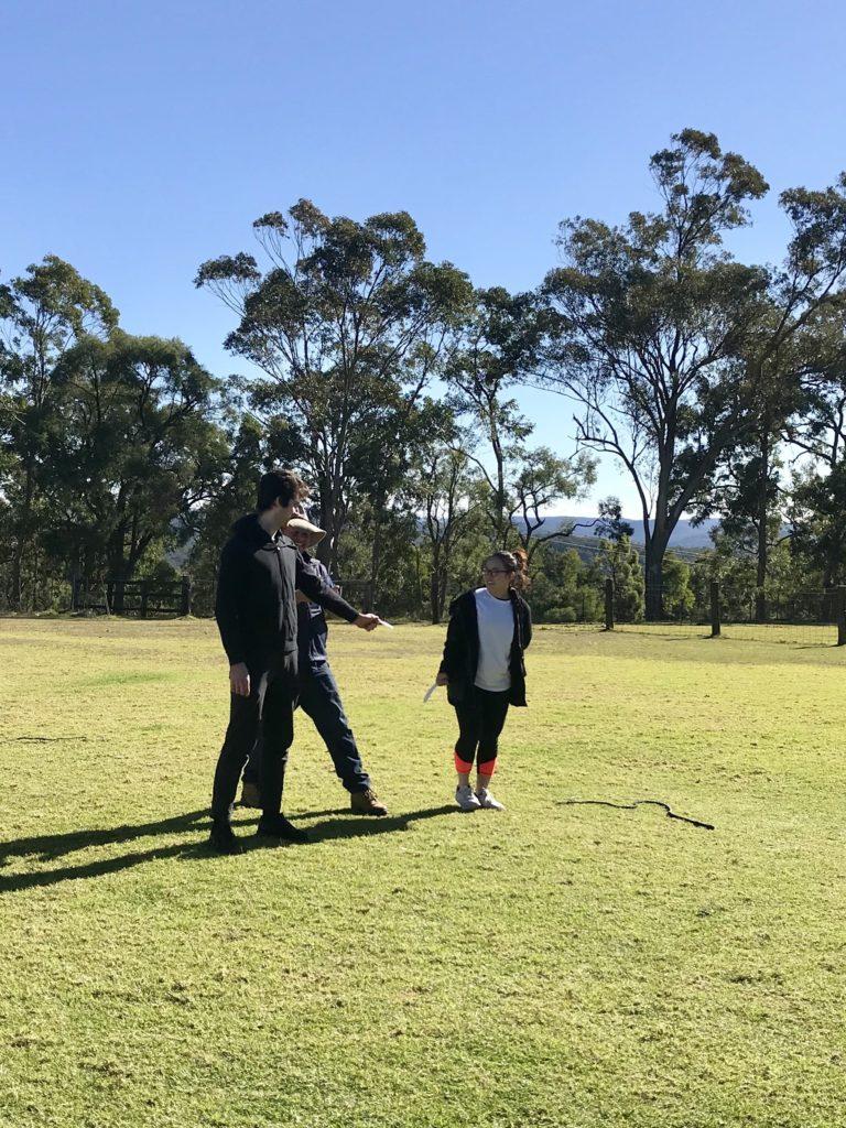 男性2人と女性が芝生に立っている