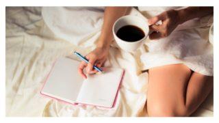 ベットの上でコーヒーを飲みながら日記を書いている女性