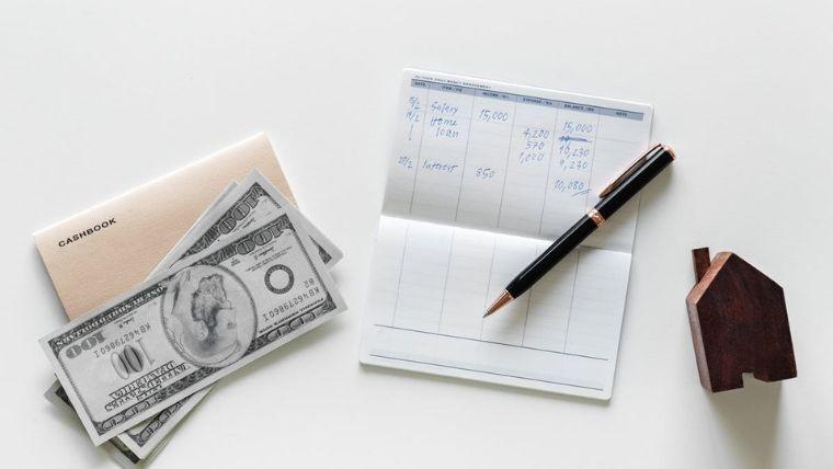白いテーブルの上にある通帳とペンと100ドル札