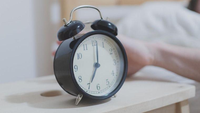 黒い目覚まし時計と止めようとしている手