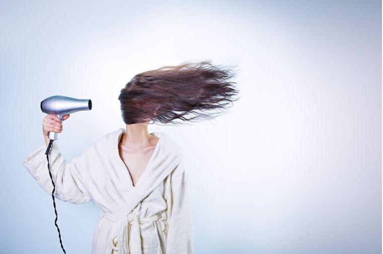 ドライヤーで髪の毛が吹き飛ばされている女性