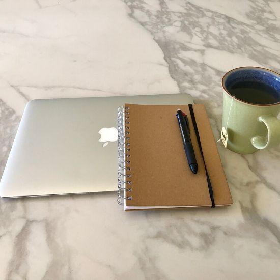 机に乗っているパソコンとノートとマグカップ