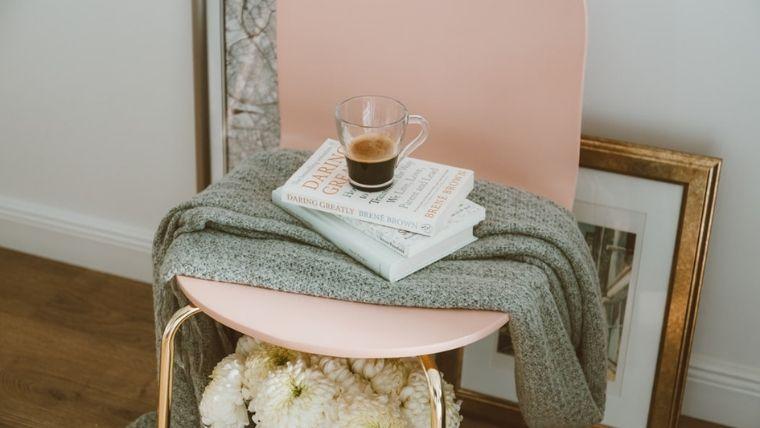 ピンクの椅子の上にあるコーヒーと本