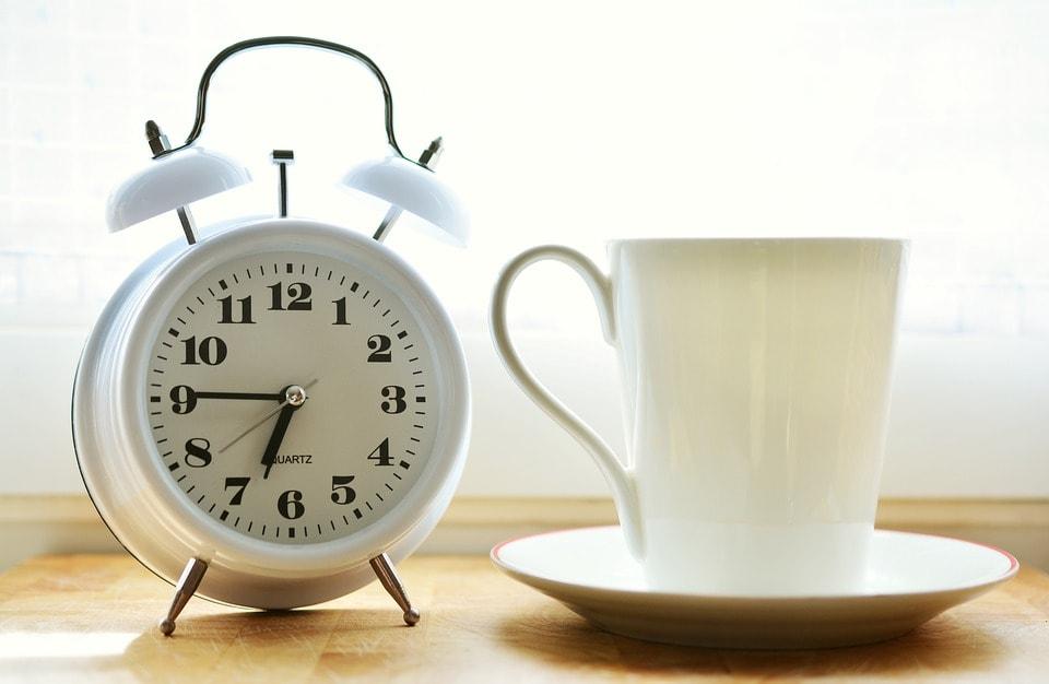 目白い覚し時計と白いコーヒーカップ