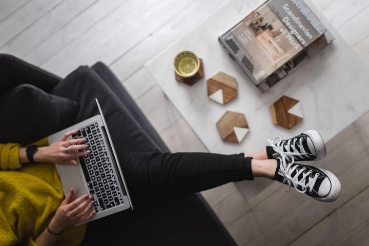 ソファーに座ってパソコンをしている女性の足