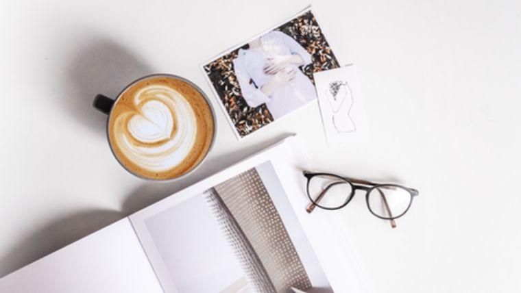 テーブの上のメガネとコヒーと雑誌と写真。