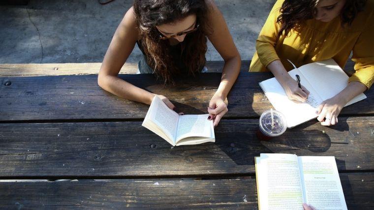 女性2人が本を読んでいる