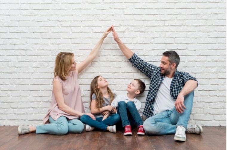 女子と男性子供2人が床に座っている
