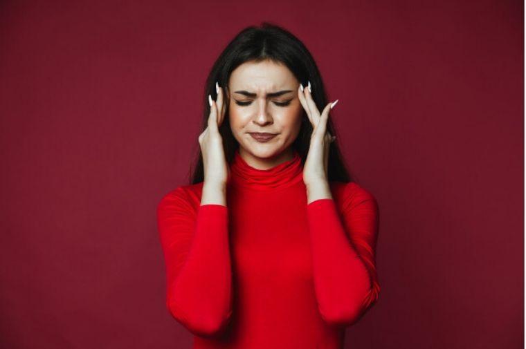 赤い服を着た女性がこめかみを押さえている