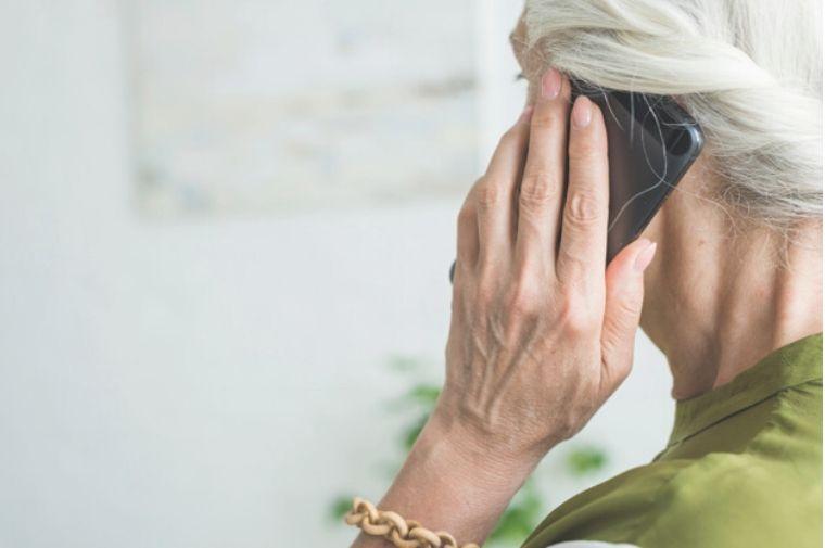 年配の女性が電話で話している