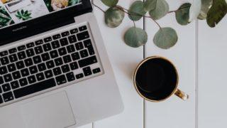 テーブルにあるコーヒーとPC