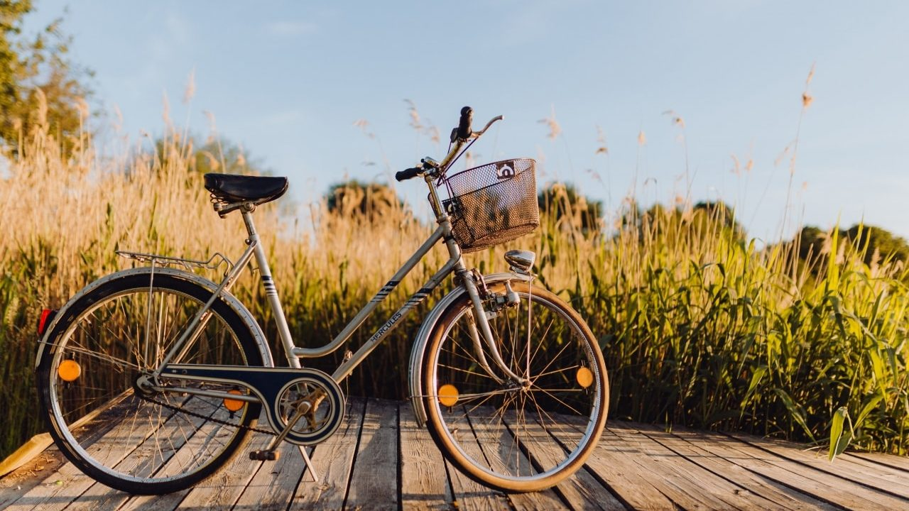 Bicycle with basket on the pier in bright sunset light-min
