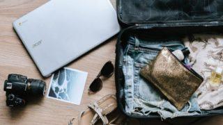 スーツケースとサングラス、パソコンが床の上に散らばっている