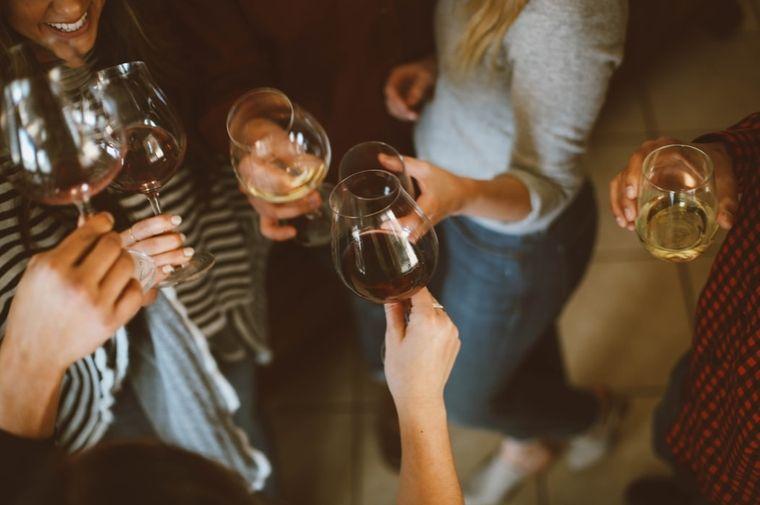 ワイングラスをもって乾杯している女性の手