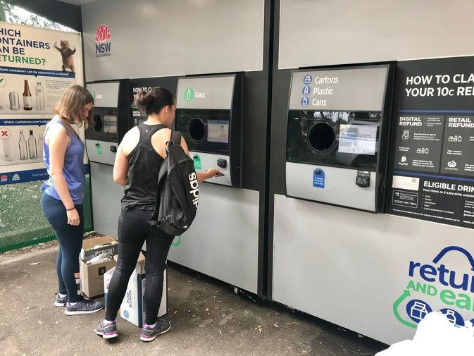 リサイクルマシーンの前にいる女性