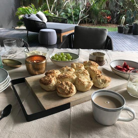 スコーンと紅茶、フルーツがテーブルにのっている