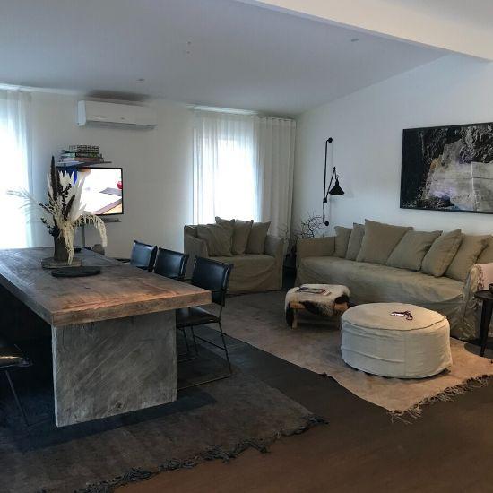 ナチュラルカラーのソファーと木の大きなテーブルが置いてあるリビング
