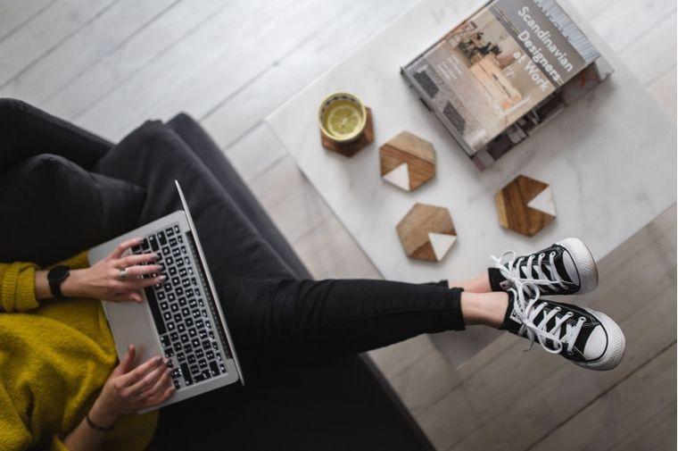 テーブルに足を乗ってけてパソコンをしている女性