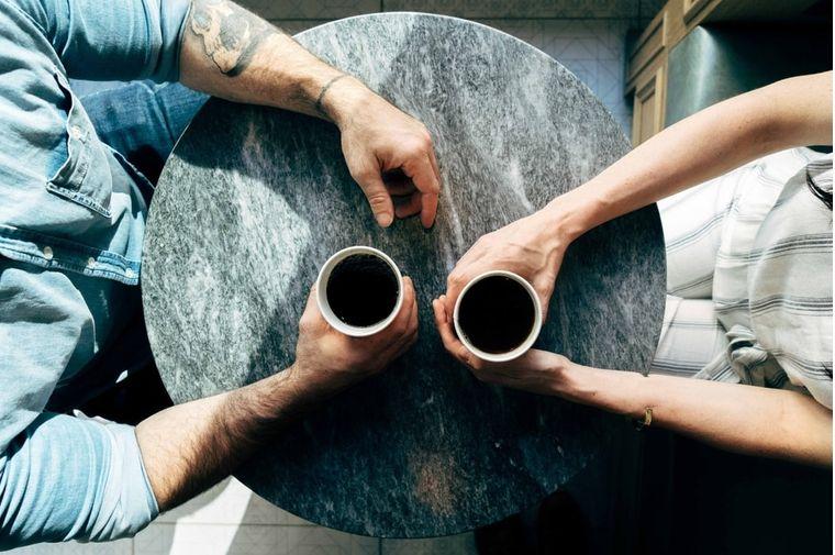 コーヒーカップを持って座っているカップルの手