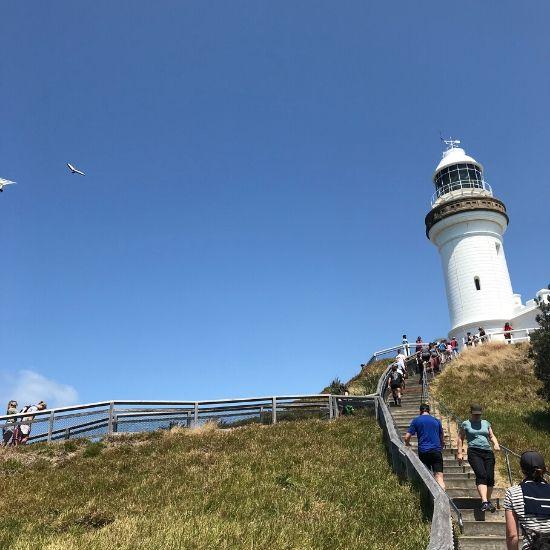 白い灯台を目指して階段を上る人たち