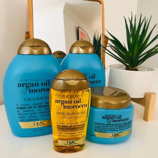 ブルーのシャンプボトルと金色にヘアオイルが鏡の前に置いていある
