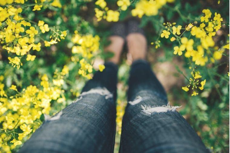 菜の花畑に立っている女性の足
