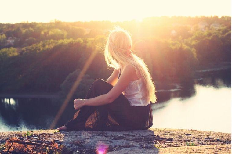 夕日を見て座っている女性