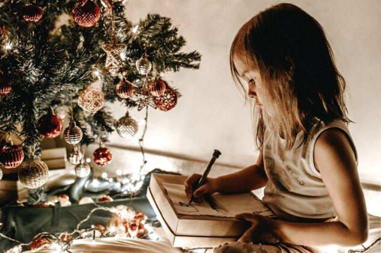 子供がツリーの前に座ってお絵描きをしている