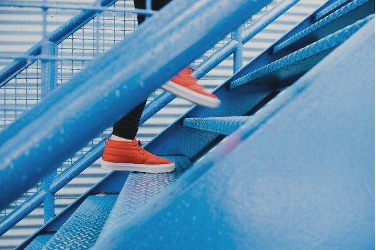 オレンジの靴を履いた人が階段を上がっていく
