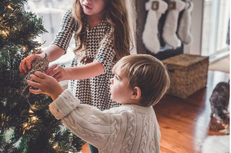 男の子と女の子がクリスマスツリーを飾っている