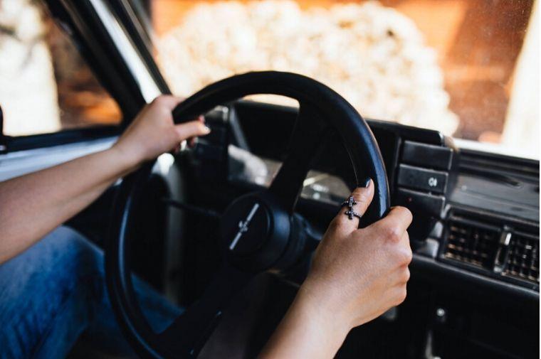 車のハンドルを握っている手