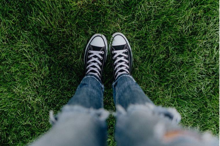 黒いスニーカーの女性が芝生の上に立っている足元。