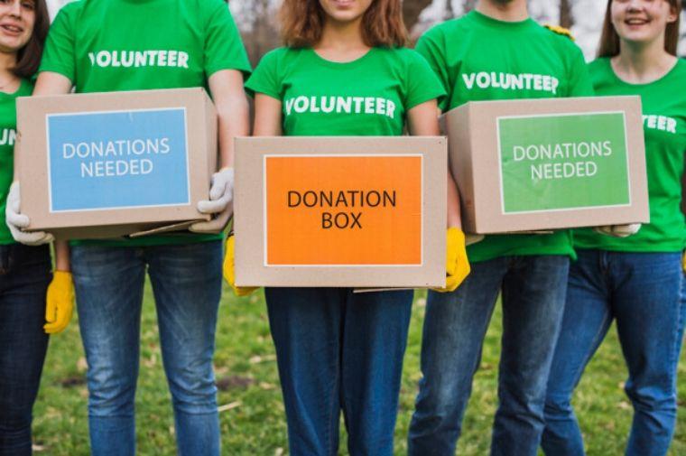 緑のTシャツを着たボランティアの人たちが箱をもって立っている