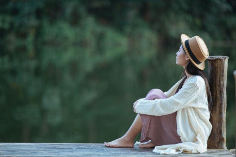 帽子をかぶった女性がデッキに座っている