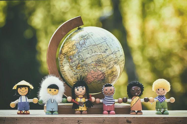 地球儀の前にある人種の違う人形が並んでいる
