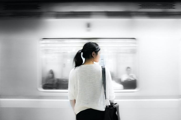 白い服を着た女性がホームで電車を待っている