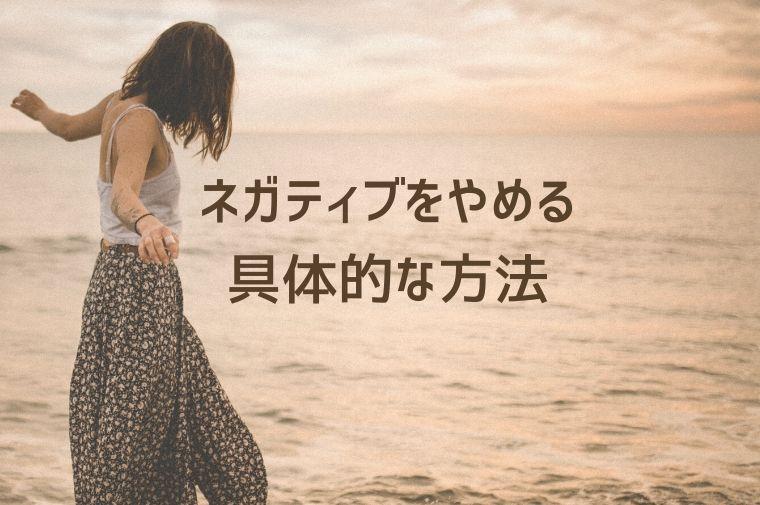 女性が下を向いて、夕方の浜辺を歩いている