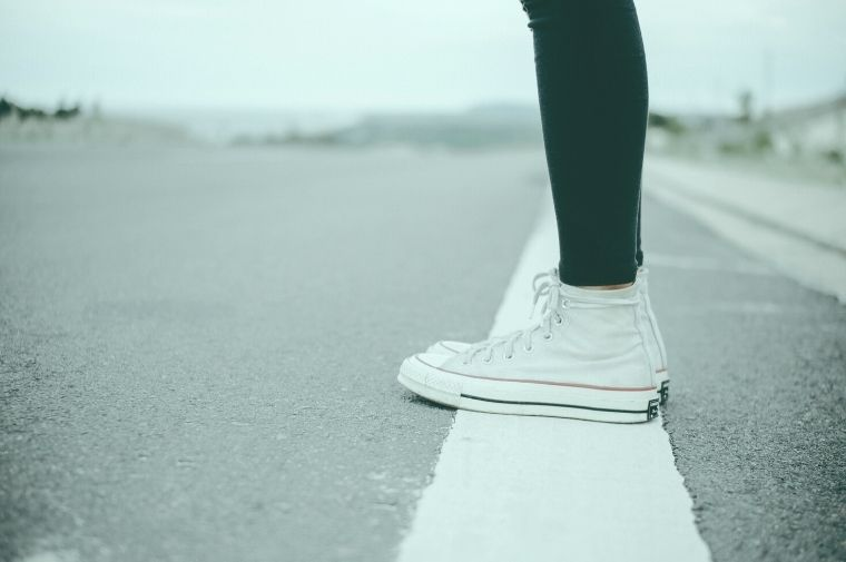 白線の上に立っている女性の足