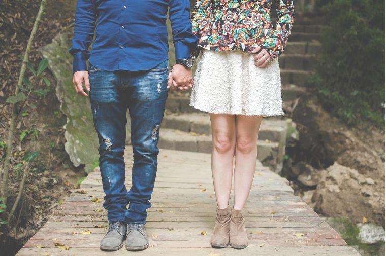 手をつないで立っているいるカップルの足