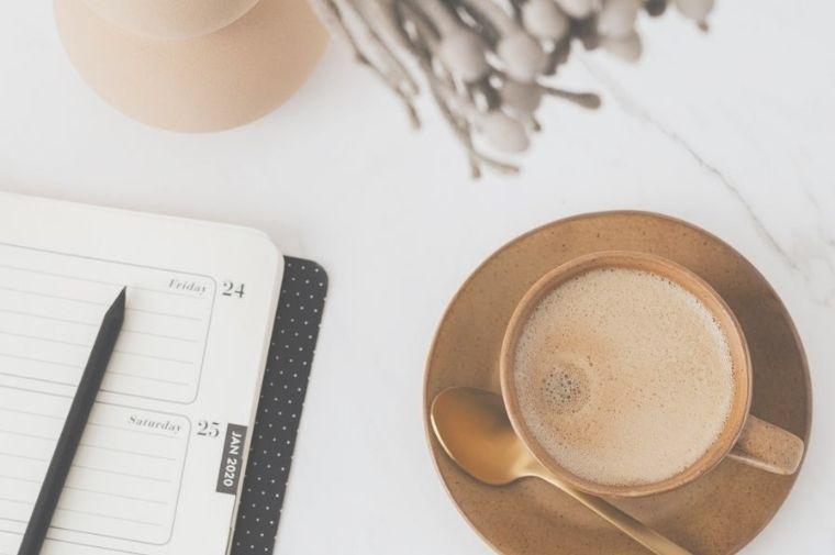 テーブルの上にあるコーヒーと日記