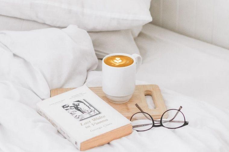 ベットの上にあるメガネと本とコーヒー