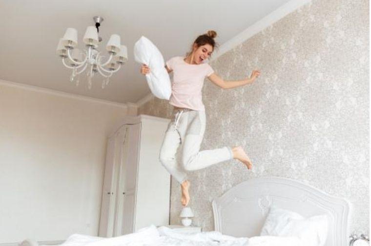 パジャマを着た女性がベットでジャンプしている