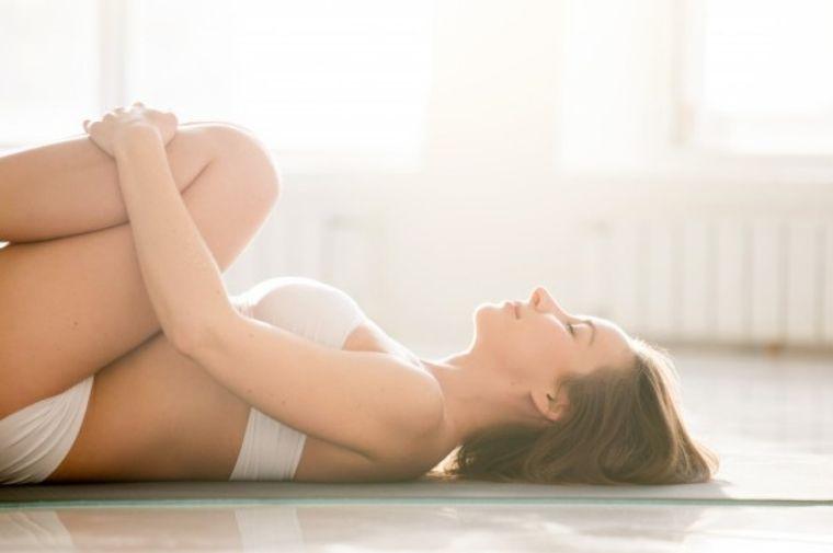 横になってストレッチをしている女性