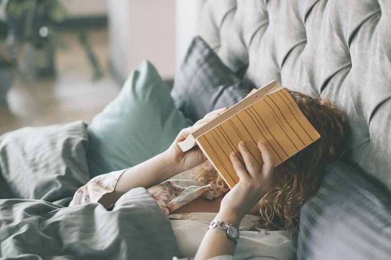 ベットで読書をしている女性