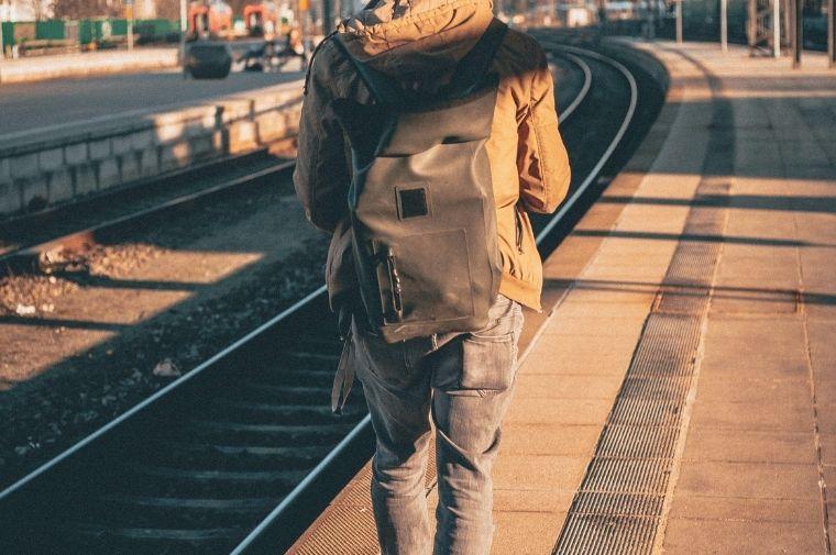 ホームで電車を待っている男性の後ろ姿