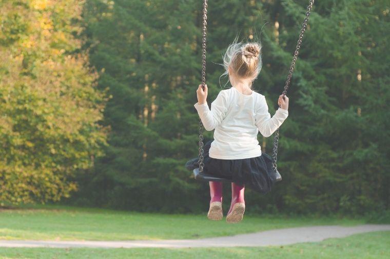 ブランコに乗っている小さい女の子の背中