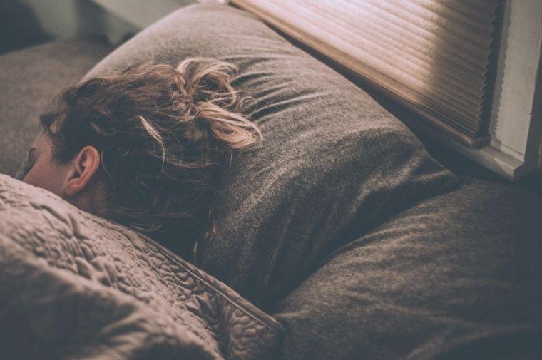 茶色いシーツの布団で寝ている女性