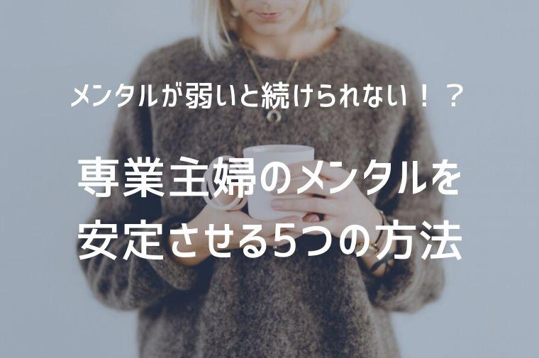 茶色いセーターを着た女性がマグカップを持って立っている