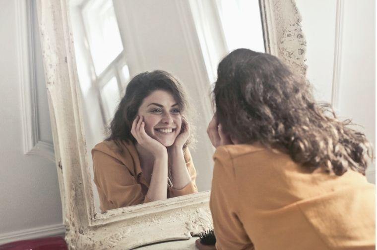 鏡に映った自分の微笑みかけている女性
