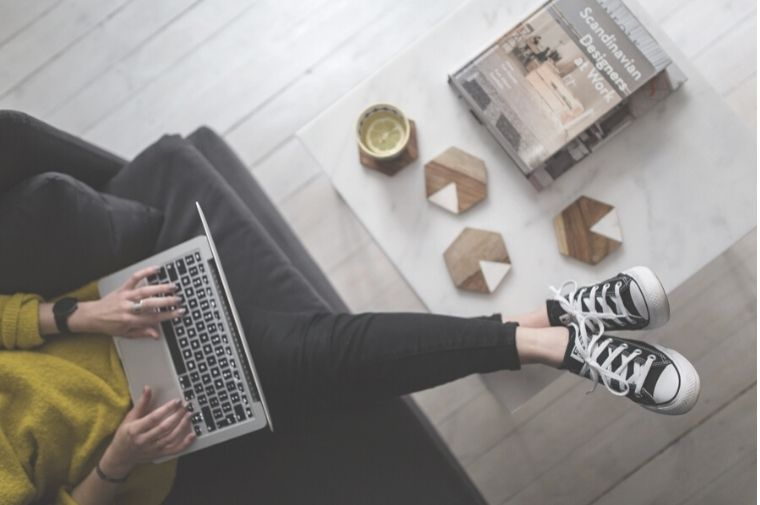 机に足を乗せてパソコンをしている女性